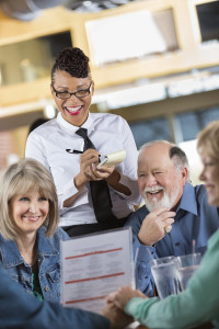 waitress-taking-order-from-table-of-senior-guests-in-restaurant